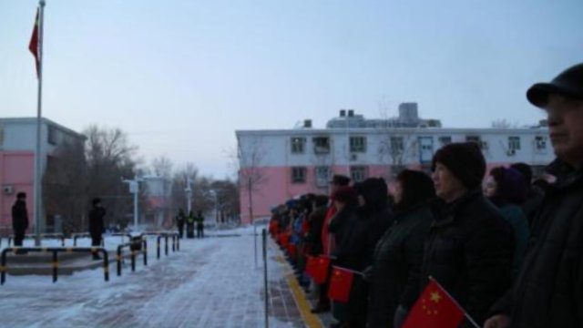 A residential community in Xinjiang organizes its residents for a flag-raising ceremony