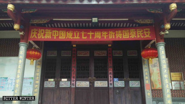 A banner hangs at the Longwo Temple entrance, celebrating the 70th anniversary of the founding of the new China.