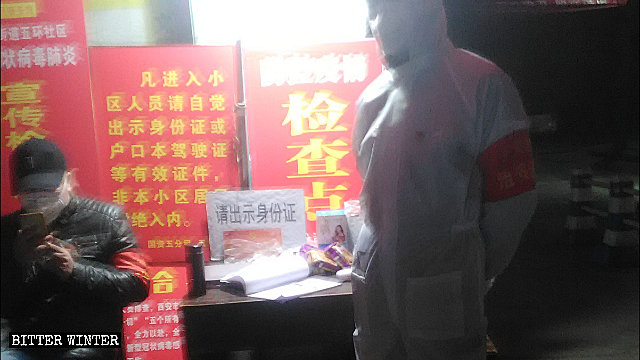 Personnel check visitors' identity in a Xi'an city's residential community.