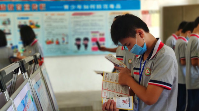 A student reads anti-xie jiao materials on a school campus in Guangdong's Enping city in June.