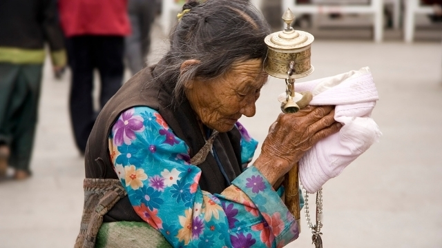 An elderly Tibetan woman praying in Lhasa, Tibet