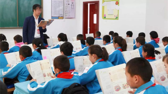 In an experimental primary school in Xinjiang, students are taught to read Chinese textbooks.