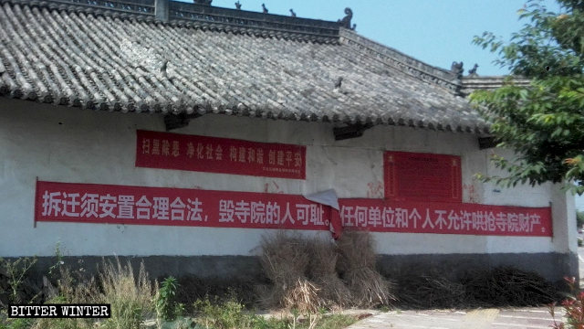 """Buddhists hung a banner, """"Appropriate and legal relocation should be guaranteed before demolition"""" on the Jinlong temple before demolition."""