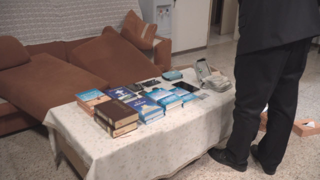 Police officers take photos of faith-related books and other items confiscated in a CAG believer's home.