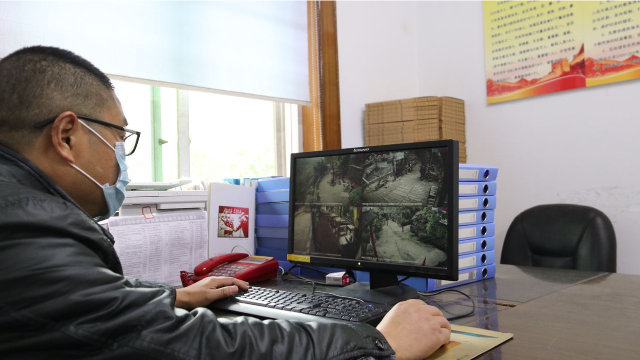 A Religious Affairs Bureau official looks at images from religious venues.