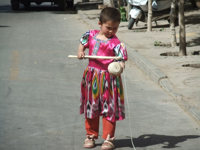Before the storm: a girl was playing with a spinning top in Hotan. Photo by Ruth Ingram.