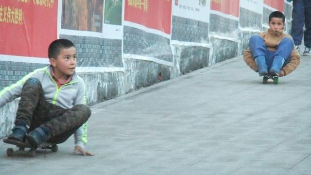 ウイグル人の少年たちは、習近平の新時代とウルムチの新中国の栄光を称賛するプロパガンダの無数の壁の1つを通り過ぎてスケートボードをしました。 ルース・イングラムによる写真。