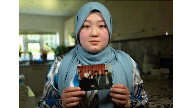 """Dilnaz Kerim, holding up a photo of her """"disappeared"""" family."""