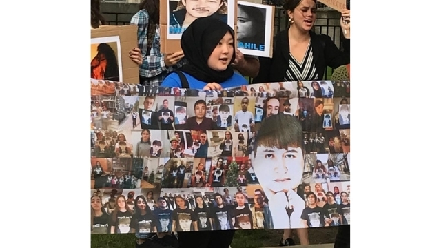 Dilnaz behind a poster raising awareness of Uyghur businessman Ekpar Asat, who vanished in 2016. There has been no news of him since.