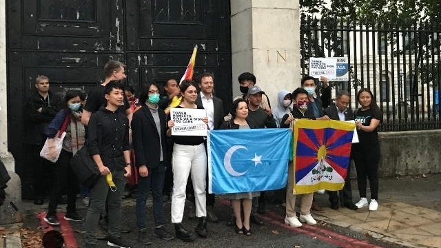 """Rahima Mahmut of the London branch of the World Uyghur Congress holding the East Turkestan flag, beside a Tibetan contingent holding theirs. """"The street names must be changed,"""" she urged, """"and the Chinese regime must be held accountable for human rights violations and genocide. It is moments like this that give me hope that people around the world are watching our suffering. And one by one they are standing up and refusing to accept"""